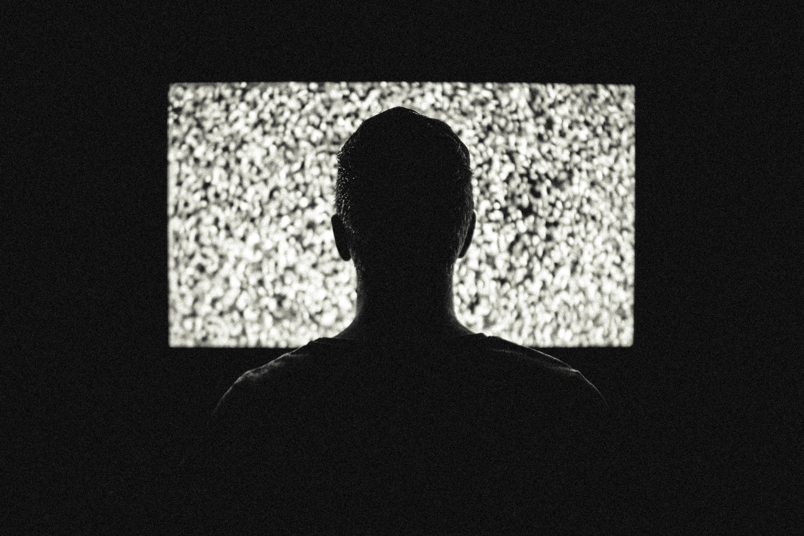 Silhouette of mans head staring at snow on a tv